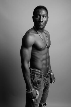 Young handsome African man shirtless against gray background