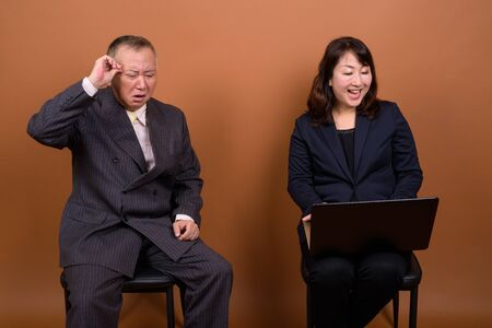 Mature Asian businessman with mature Asian businesswoman using laptop