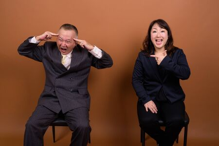 Mature Asian businessman and mature Asian businesswoman having different opinions together