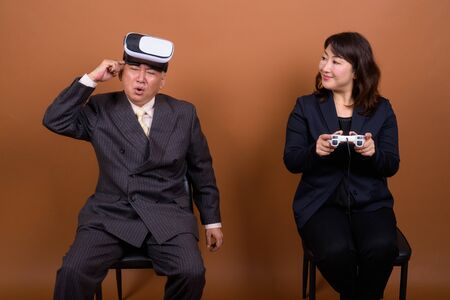 Mature Asian businesswoman with mature Asian businessman playing games