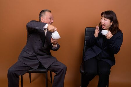 Mature Asian businessman and mature Asian businesswoman drinking coffee together