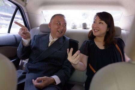 Mature Asian businessman and mature Asian woman riding car together