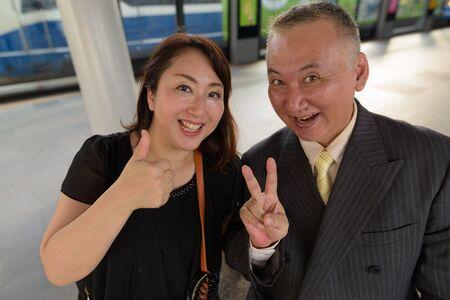 Mature Asian businessman and mature Asian woman exploring the city together
