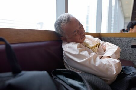 Portrait of mature Japanese businessman relaxing inside the restaurant at the mall