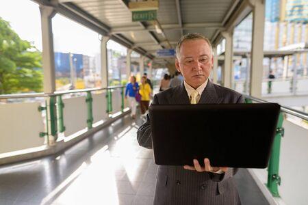 Portrait of mature Asian businessman exploring the city