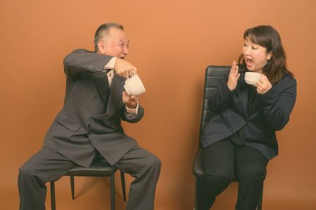 Mature Asian businessman and mature Asian businesswoman together against brown background