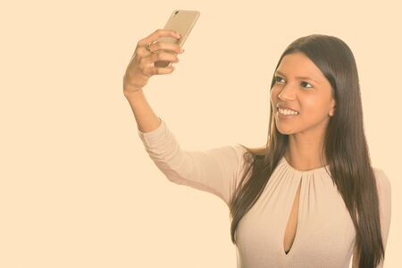 Studio shot of young happy Brazilian woman smiling while taking selfie with mobile phone