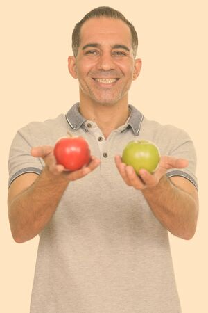 Mature happy Persian man holding red and green apple