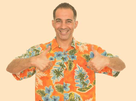 Mature happy Persian man ready for vacation giving thumbs up