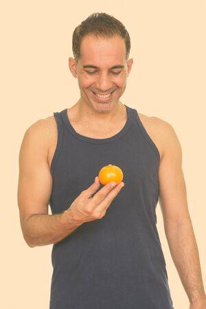Portrait of happy mature Persian man holding orange