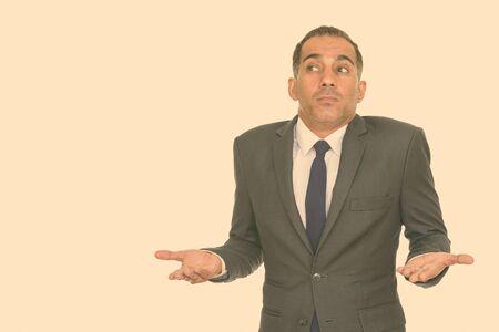 Portrait of confused mature Persian businessman shrugging shoulders