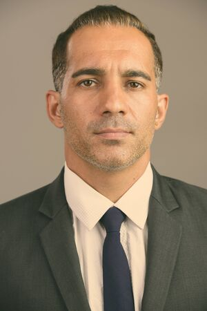 Face of mature Persian businessman in suit looking at camera