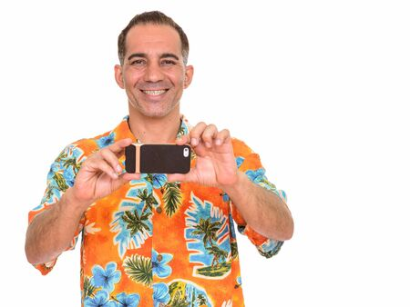 Portrait of happy mature Persian tourist man taking picture with phone