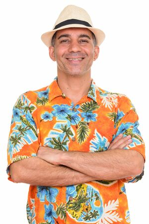 Portrait of happy mature Persian tourist man smiling with arms crossed