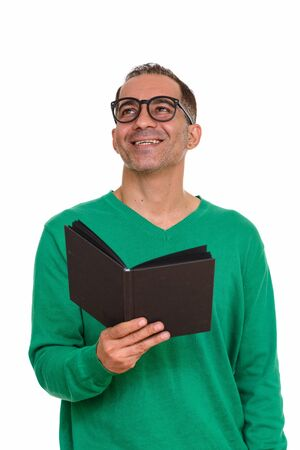 Mature happy Persian man holding book while thinking