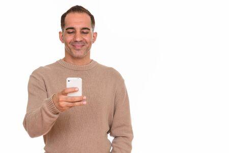 Mature happy Persian man using mobile phone