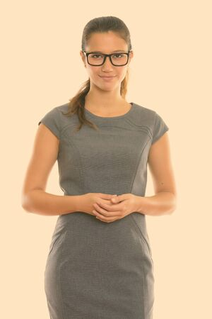 Studio shot of young beautiful businesswoman wearing eyeglasses with hands together Banque d'images