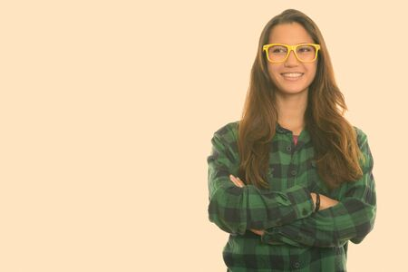 Studio shot of young happy woman smiling and thinking while wearing eyeglasses with arms crossed