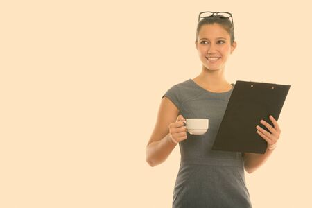 Young happy businesswoman smiling and thinking while holding clipboard and coffee cup