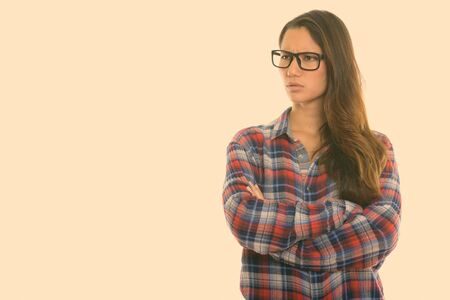 Studio shot of young angry woman thinking with arms crossed while wearing eyeglasses