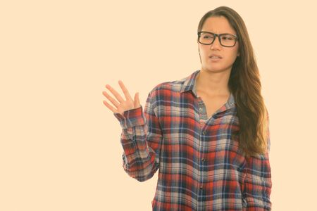 Studio shot of young disgusted woman wearing eyeglasses and showing stop hand sign at distance