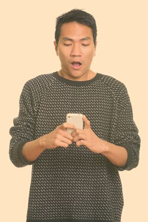 Studio shot of young Asian man looking shocked while using mobile phone