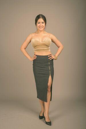 Joven hermosa mujer asiática sobre fondo gris Foto de archivo