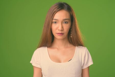 Young slim Asian woman against green background