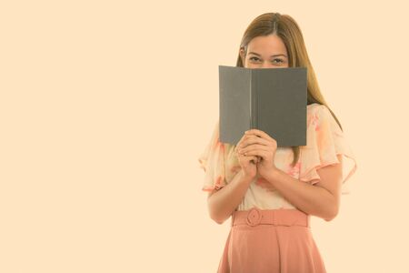 Studio shot of young beautiful woman hiding behind book