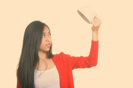 Studio shot of young Asian teenage girl holding empty coffee cup upside down