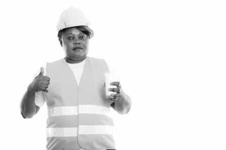 Studio shot of fat black African woman construction worker holding glass of milk and giving thumb up