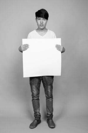 Young Asian teenage boy holding white board against gray background 版權商用圖片