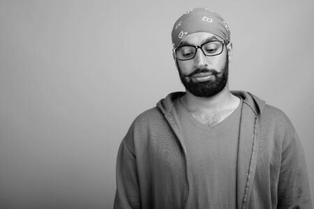 Portrait of young handsome bearded Indian man with eyeglasses