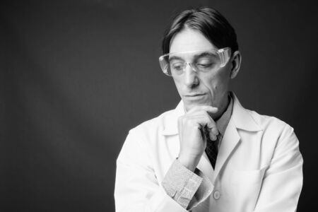 Mature handsome Italian man doctor wearing protective glasses Banque d'images