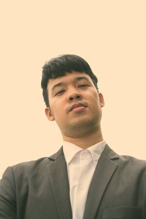 Young Asian businessman against view of the city