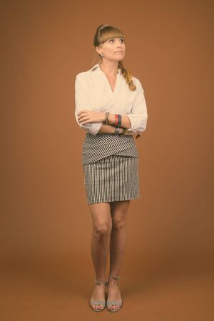 Portrait of young beautiful businesswoman against brown background