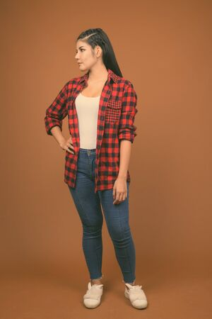Young beautiful Asian woman wearing red checkered shirt against brown background