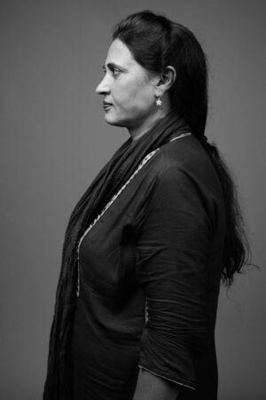 Mature beautiful Indian woman against gray background Archivio Fotografico