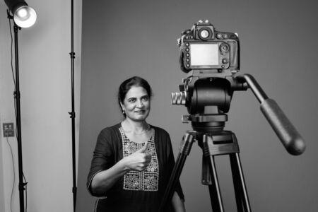 Studio shot of mature beautiful Indian woman vlogging