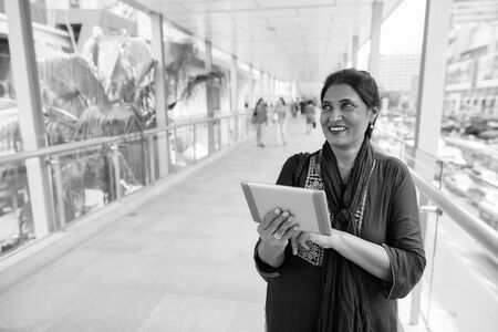 Happy mature beautiful Indian woman exploring the city