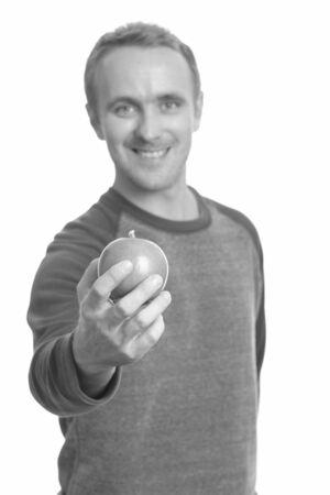 Portrait of happy handsome man holding apple
