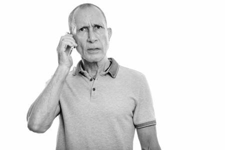 Studio shot of angry senior man talking on mobile phone
