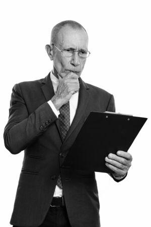 Studio shot of senior businessman reading on clipboard while thinking