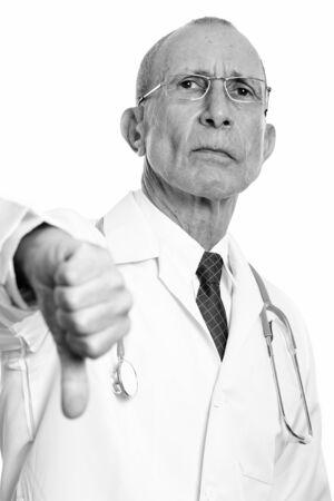 Studio shot of senior man doctor giving thumb down