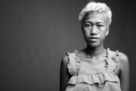 Young beautiful rebellious woman with short hair against gray background 版權商用圖片