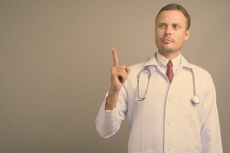 Portrait of handsome man doctor against gray background