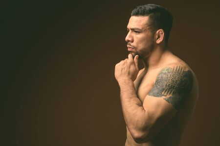Young muscular Hispanic man shirtless against brown background Reklamní fotografie