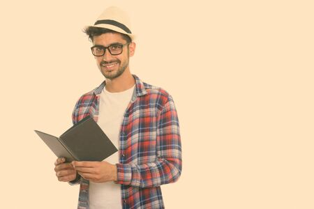 Studio shot of young happy Persian man smiling while holding book