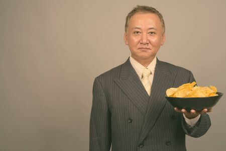 Portrait of mature Asian businessman with bowl of potato chips