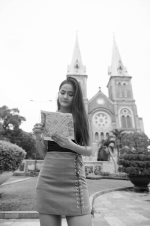Young beautiful Asian tourist woman looking at the map against view of cathedral Stock Photo
